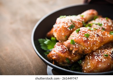 Baked spicy chicken legs with sesame and parsley in cast iron frying pan on dark wooden background close up.
