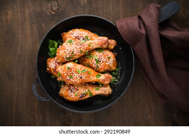 Baked spicy chicken legs with sesame and parsley in cast iron frying pan on dark wooden background top view.