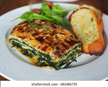 Baked Spinach with cheese served with garlic bread.
