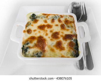 Baked spinach and cheese with spoon and fork on the white background.