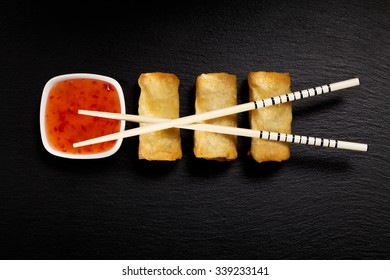 Baked spring rolls with deep, rice and vegetables, on a black plate