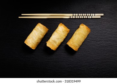 Baked spring rolls with vegetables, on a black plate