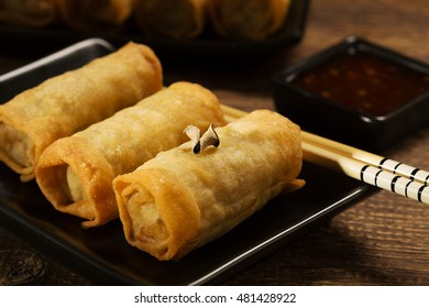 Baked spring rolls with vegetables on a black plate.