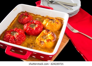 Baked stuffed peppers with minced meat, rice, in sauce on the black background