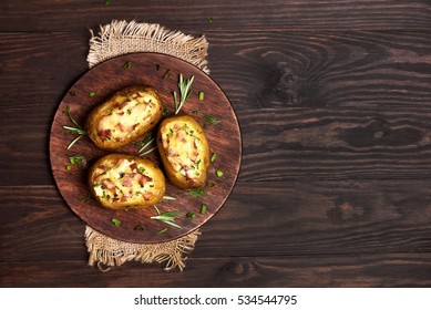 Baked stuffed potato with bacon, cheese and green onion on wooden background with copy space