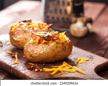 Baked stuffed potatoes with bacon, cheddar, mushrooms and dill on wooden table