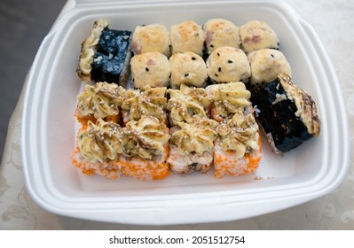 Baked sushi rolls on a white tray close up
