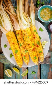 baked sweet corn cobs with herb butter and lime on wooden table