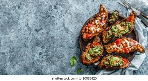 Baked sweet potato toast with roasted chickpeas, tomatoes, goat cheese, sauce guacamole, avocado, seedlings on wooden board over blue background. Healthy vegan food, clean eating, dieting, top view
