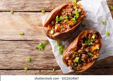 Baked sweet potatoes stuffed with ground beef with tomatoes and onions on paper on a table. Horizontal top view from above