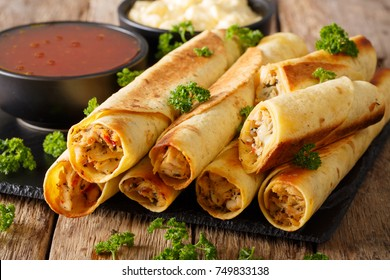 Baked taquitos with chicken and cheese close-up on the table. horizontal