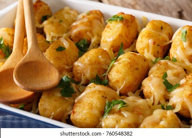 Baked Tater Tots with cheese and herbs close up in a dish baking dish on the table. horizontal