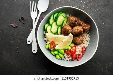 Baked teriyaki meat balls with brown rice, cucumbers, hot pepper, lemon slices in a bowl. Top View