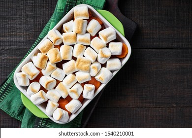 Baked thanksgiving sweet potato casserole with marshmallow topping, on a wooden cutting board with a green kitchen dish towel on a wooden table, copy space, horizontal, close-up