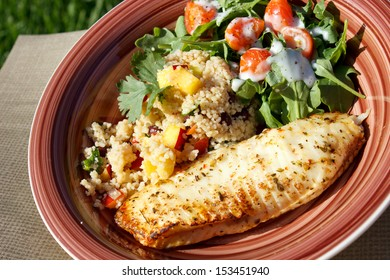 Baked tilapia served with arugula and quinoa salad