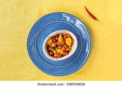 Baked tomato in bowl on blue plate and yellow background with chilli pepper