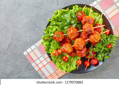 baked in tomato sauce meatballs on skewers with fresh tomatoes on a bed of lettuce leaves on a black plate, horizontal view from above, flat lay