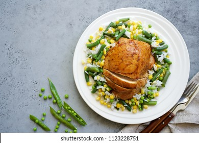 Baked turkey breast with vegetables and rice on a plate. Gray food background. Diet food