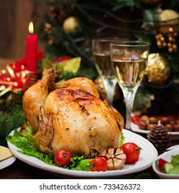 Baked turkey or chicken. The Christmas table is served with a turkey, decorated with bright tinsel and candles. Fried chicken, table. Christmas dinner