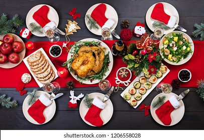 Baked turkey. Christmas dinner. The Christmas table is served with a turkey, decorated with bright tinsel and candles. Fried chicken, table.  Family dinner. Top view