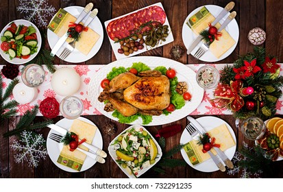 Baked turkey. The Christmas table is served with a turkey, decorated with bright tinsel and candles. Fried chicken, table. Christmas dinner. Flat lay. Top view