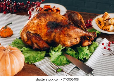 Baked turkey on green salad leaves with fried vegetables on a wooden table