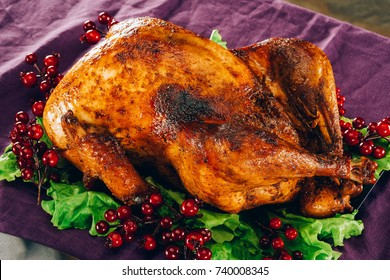 Baked turkey on salad leaves with cranberries on violet tablecloth for thanksgiving day