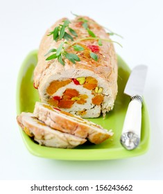 Baked turkey roll stuffed with dried apricots, cherries and pistachios, shallow depth of field, selective focus