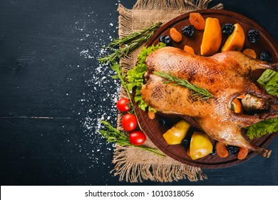 Baked turkey with vegetables and spices. Thanksgiving day. Goose chicken grill. On a wooden background. Top view.