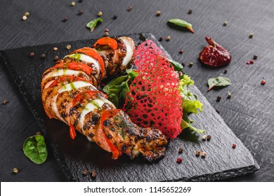 Baked Veal with mozzarella cheese, tomatoes, pesto sauce and green salad on black sbackground. Hot Meat Dishes. Top view, flat lay