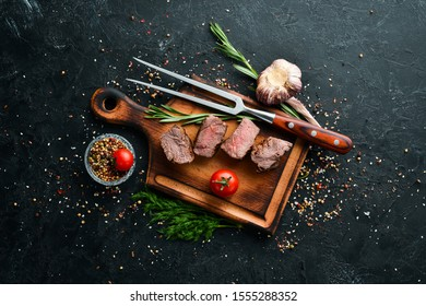 Baked veal on a fork. Veal steak on black stone background. Top view. Free space for your text.
