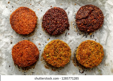 Baked vegan burgers, cutlets made of beetroot, green peas, carrots, groats and herbs on white parchment, top view