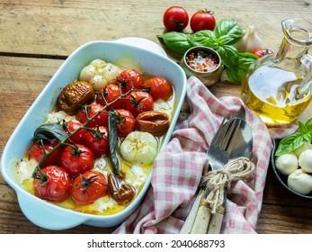 Tomate de légumes cuite, basilic, fromage à la mozzarella, ail dans le four en céramique. cuisine, plat cuisiné