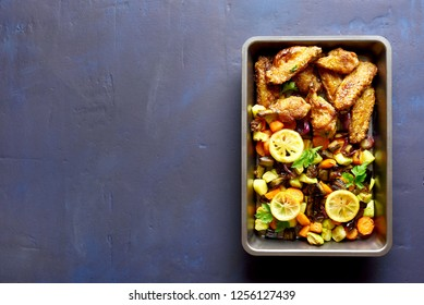 Baked vegetables with chicken wings in baking tray on stone background with copy space. Top view, flat lay