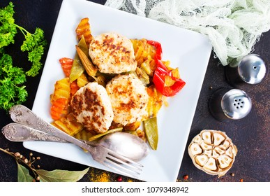 baked vegetables with cutlet on white plate
