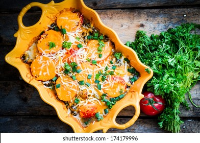Baked vegetables in a dish on wooden background