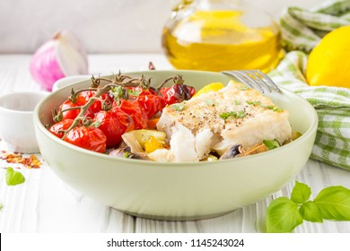 Baked vegetables with mushrooms and white fish fillets in a bowl. Zucchini, cherry tomatoes on a branch, red onions, bell peppers and garlic. Healthy diet food