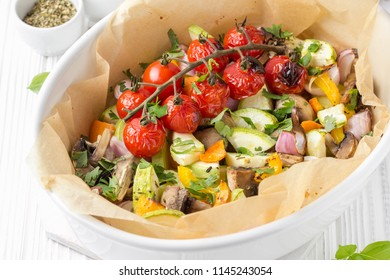 Baked vegetables with mushrooms in white. Zucchini, cherry tomatoes on a branch, red onions, bell peppers and garlic. Delicious garnish, vegetarian food, healthy diet