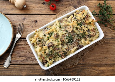 baked vegetarian pasta with mushroom and cheese on kitchen table background