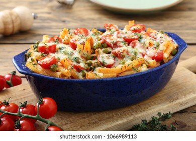 baked vegetarian pasta with vegetables and cheese on kitchen table background