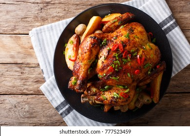 Baked whole chicken with mushrooms and potatoes close-up on a plate on a table. Horizontal top view from above