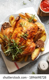 baked whole chicken with rosemary, garlic and ketchup on gray concrete background. roasted chicken.
