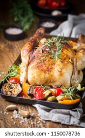 Baked whole chicken with vegetables and herbs close-up on a plate on a table.