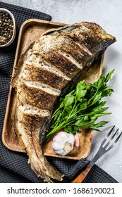 Baked whole fish haddock on a cutting Board. Gray background. Top view