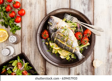 Baked whole fish, served with roasted vegetables and lemon. Top view.