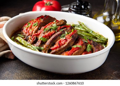Baked whole pork meat with tomatoes, green beans and black olives, homemade cozy winter dish in a pot. Christmas food, delicious main course