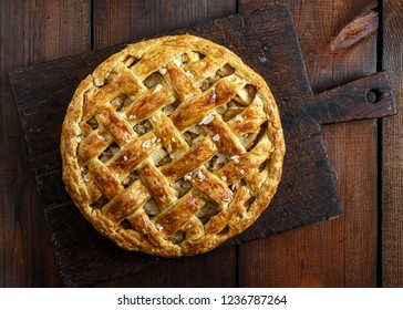 baked whole round apple pie on a brown wooden board, puff pastry, top view