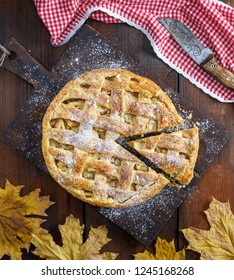Baked whole round apple pie on a rectangular old brown board, wooden table, top view