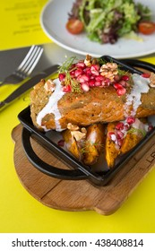 Baked wild salmon filet with a falafel spiced coat, a walnut and pomegranate salsa, served with roasted sweet potatoes in a metal dish.
