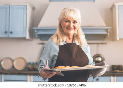 I baked with for you with love. Waist up portrait of kind granny treating with appetite pastry. She is standing in kitchen and laughing